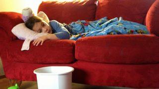 Child lying on sofa with flu