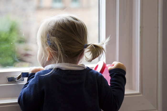 Young girl looking out window at YourGP children's clinic