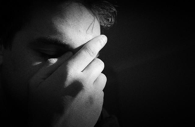 Depressed man holding face