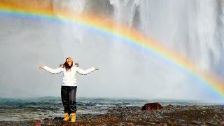 happy woman standing under rainbow