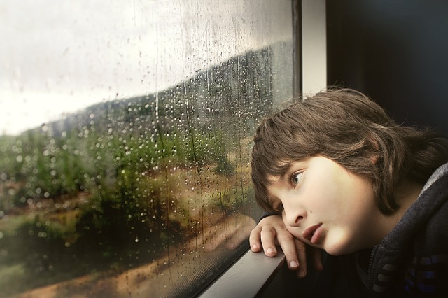 upset child looking out train window